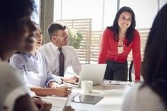 Femme d'affaires hispanique écoutant des collègues lors d'une réunion photographie stock