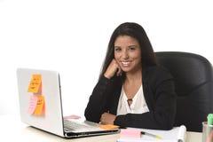 Femme d'affaires hispanique attirante s'asseyant au bureau travaillant au sourire d'ordinateur portable d'ordinateur heureux Images stock