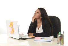 Femme d'affaires hispanique attirante s'asseyant au bureau travaillant au sourire d'ordinateur portable d'ordinateur heureux Photographie stock libre de droits