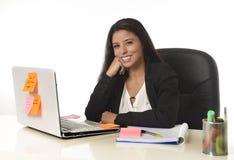 Femme d'affaires hispanique attirante s'asseyant au bureau travaillant au sourire d'ordinateur portable d'ordinateur heureux Photos libres de droits