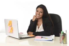 Femme d'affaires hispanique attirante s'asseyant au bureau travaillant au sourire d'ordinateur portable d'ordinateur heureux Photos stock