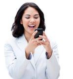 Femme d'affaires hispanique heureuse envoyant un texte photographie stock libre de droits
