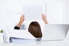 Femme d'affaires Holding Blank Paper avec la reliure et ordinateur portable sur le bureau Photographie stock
