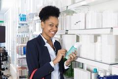 Femme d'affaires Holding Medicine Bottle dans la pharmacie photographie stock