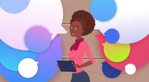 Femme d'affaires Holding Tablet Speak d'afro-américain au-dessus des bulles colorées de causerie Images stock