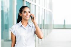 Femme d'affaires indienne à l'aide du téléphone près du bureau Image stock