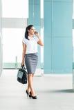 Femme d'affaires indienne à l'aide du téléphone près du bureau Images stock