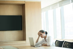 Femme d'affaires inquiétée à l'aide de l'ordinateur portable dans la salle de conférence photographie stock