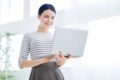 Femme d'affaires intelligente avec plaisir regardant l'écran d'ordinateur portable Photographie stock