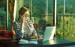 Femme d'affaires intelligente dans les vêtements décontractés travaillant sur l'ordinateur Photos libres de droits