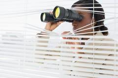 Femme d'affaires jetant un coup d'oeil avec des jumelles par des abat-jour Photographie stock libre de droits