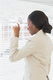 Femme d'affaires jetant un coup d'oeil par des abat-jour dans le bureau Photo libre de droits