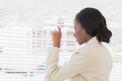 Femme d'affaires jetant un coup d'oeil par des abat-jour de bureau Photographie stock