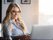 Femme d'affaires joyeuse dactylographiant sur l'ordinateur portable dans le bureau Photos stock