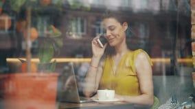 Femme d'affaires joyeuse parlant au téléphone portable et à l'aide de l'ordinateur portable dans le cafétéria banque de vidéos