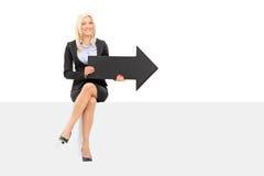 Femme d'affaires jugeant la flèche noire posée sur le panneau Photographie stock