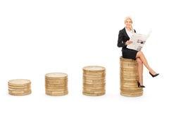 Femme d'affaires lisant les actualités posées sur des pièces de monnaie Photos stock