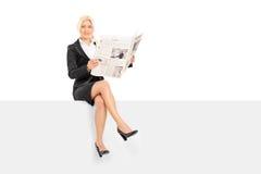 Femme d'affaires lisant les actualités posées sur un panneau Photo libre de droits