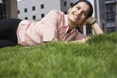 Femme d'affaires Listening Music While se trouvant sur l'herbe Images stock