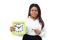 Femme d'affaires mécontente dirigeant le doigt sur l'horloge Images stock