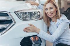 Femme d'affaires mûre choisissant la nouvelle automobile au concessionnaire photos stock