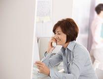 Femme d'affaires mûre parlant au téléphone de ligne terrestre photographie stock libre de droits