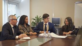 Femme d'affaires mûre présent le projet aux collègues multi-ethniques à l'aide de l'ordinateur portable dans le bureau banque de vidéos