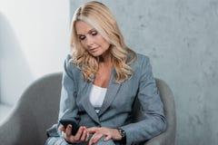 femme d'affaires mûre réfléchie à l'aide du smartphone tout en se reposant photographie stock libre de droits