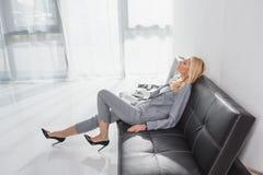 Femme d'affaires mûre s'asseyant sur le divan Photographie stock libre de droits
