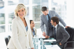 Femme d'affaires mûre avec des collègues discutant dans le bureau Image stock