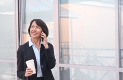 Femme d'affaires m?re ayant une coupure devant un immeuble de bureaux, parlant au t?l?phone et buvant du caf? photo libre de droits