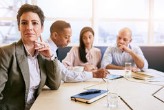 Femme d'affaires mûre regardant l'appareil-photo au cours de la réunion d'affaires Image stock