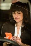 Femme d'affaires mûres regardant pour téléphoner dans la voiture Images libres de droits
