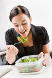 Femme d'affaires mangeant de la salade au bureau Photos libres de droits