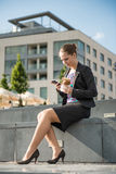 Femme d'affaires mangeant et travaillant avec le téléphone Photos libres de droits