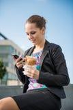 Femme d'affaires mangeant et travaillant avec le téléphone Image stock
