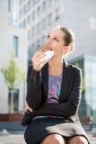 Femme d'affaires mangeant la coupure Images libres de droits