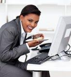 Femme d'affaires mangeant un eclair au travail Photographie stock