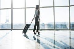 Femme d'affaires marchant avec des bagages dans l'aéroport Image stock