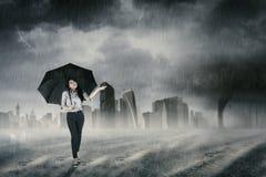 Femme d'affaires marchant avec le parapluie sous la pluie Photographie stock libre de droits
