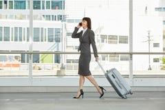 Femme d'affaires marchant et parlant au téléphone portable avec la valise Photographie stock libre de droits