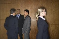 Femme d'affaires marchant par Businessmen Images stock