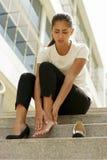 Femme d'affaires marchant sur des talons hauts sentant la douleur aux bas de la page Photo stock