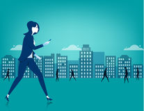 Femme d'affaires marchant sur la ville utilisant un téléphone intelligent Photographie stock libre de droits