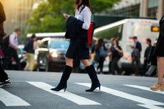Femme d'affaires marchant sur le passage piéton et textotant sur le smartphone dans la rue de ville Photo stock