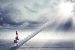 Femme d'affaires marchant vers le haut de l'escalier à la porte en ciel avec briller léger lumineux vers le bas Images libres de droits