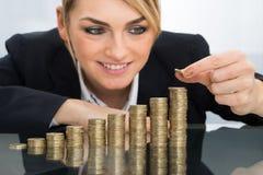 Femme d'affaires mettant la pièce de monnaie sur la pile de pièces de monnaie photos libres de droits