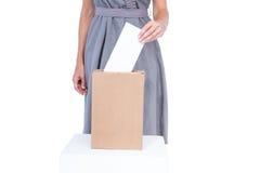 Femme d'affaires mettant le vote dans la boîte de vote Images libres de droits