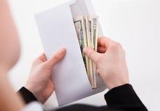 Femme d'affaires mettant les billets de banque américains dans l'enveloppe photographie stock