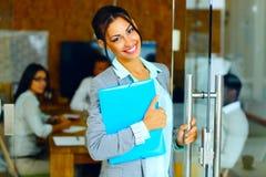 Femme d'affaires mignonne de sourire se tenant avec le dossier Images stock